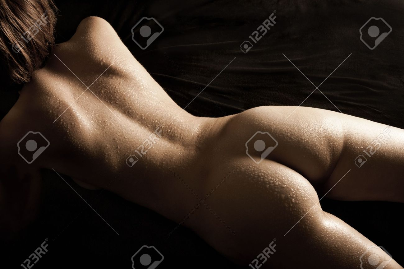 Beautiful back of nude young woman with wet body lying on black mattress, sepia toned image Stock Photo - 9465805