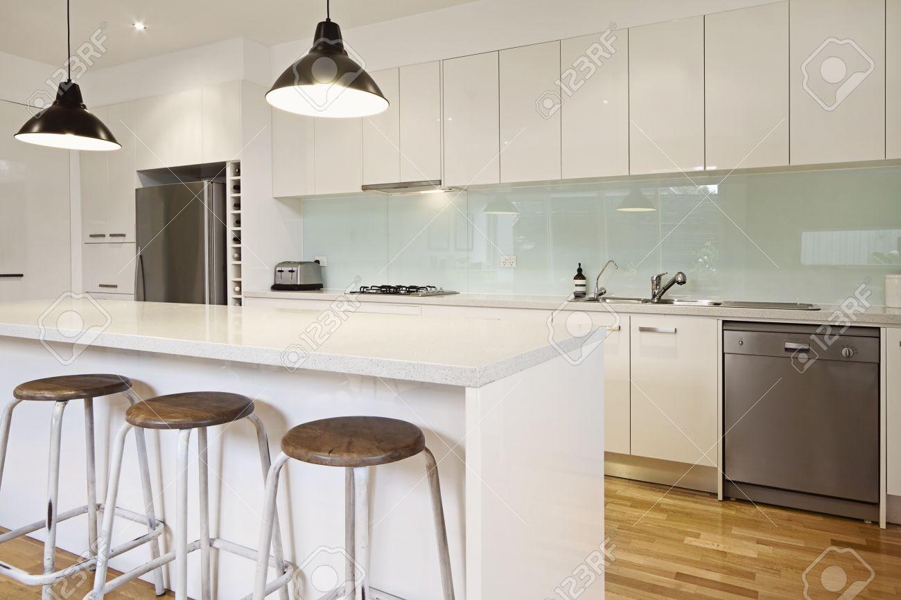 Witte moderne keuken met kookeiland en barkrukken royalty vrije ...