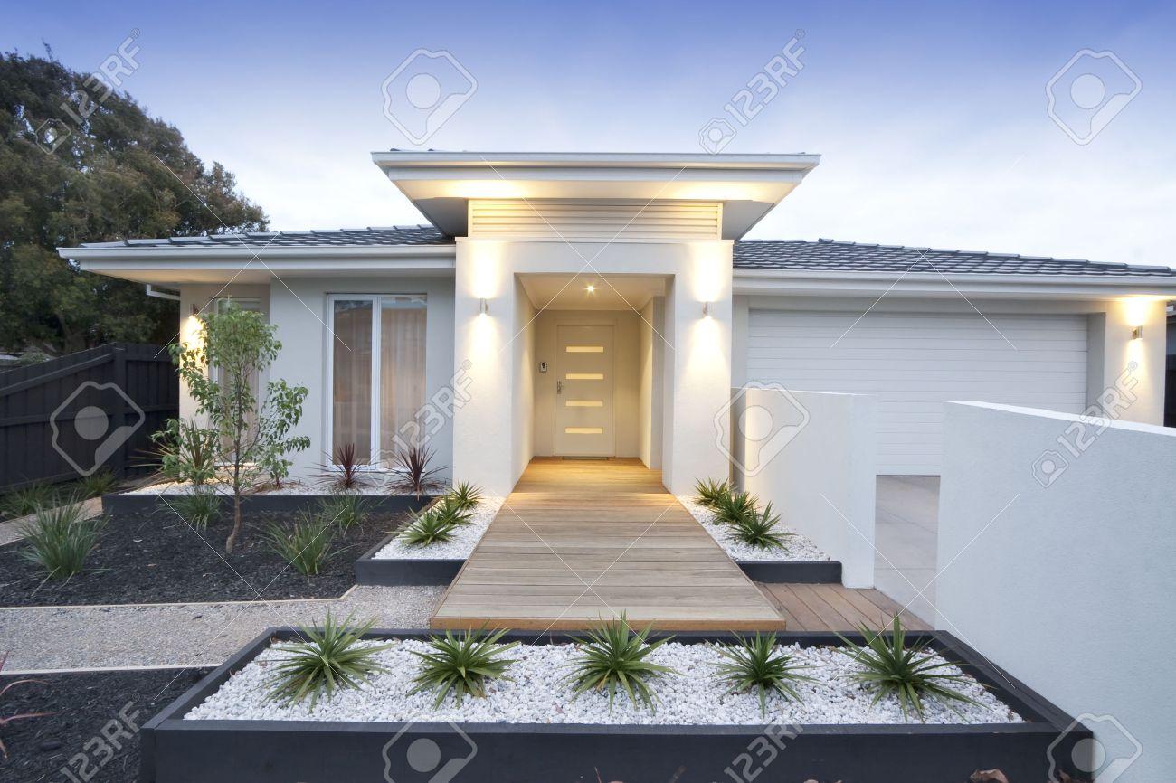 Gevel en toegang tot een eigentijdse witte weergegeven thuis in
