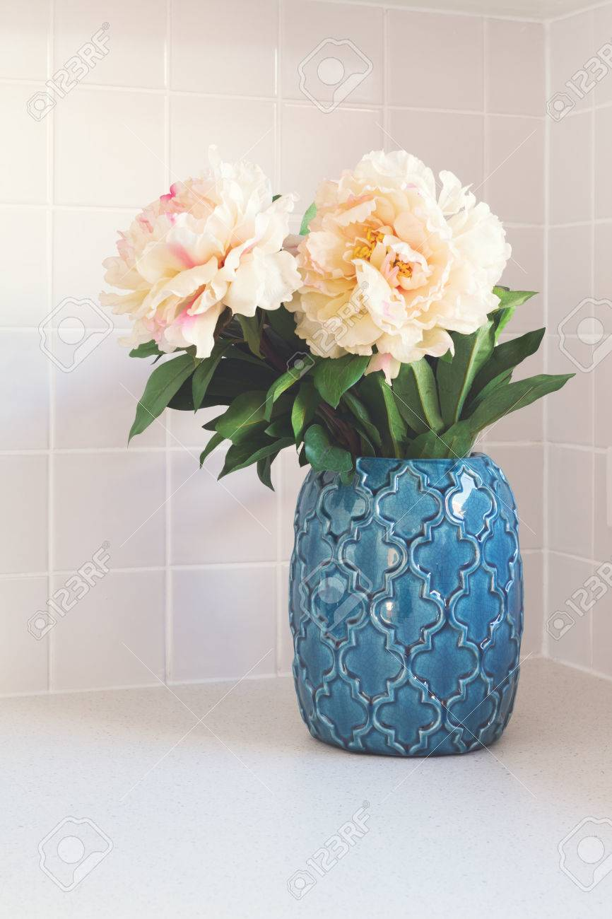 Blue Moroccan Vase With Large White Flowers On Kitchen Bench Stock