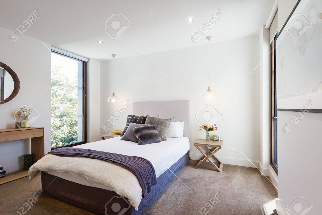 Luxury interior designed bedroom with comfy pillows and throw rug and pendant lights stock photo