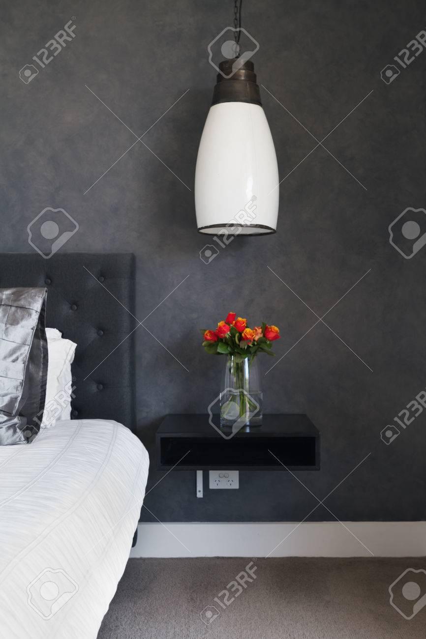 Orange roses sur la table de chevet design contemporain de chambre sombre  avec éclairage pendentif