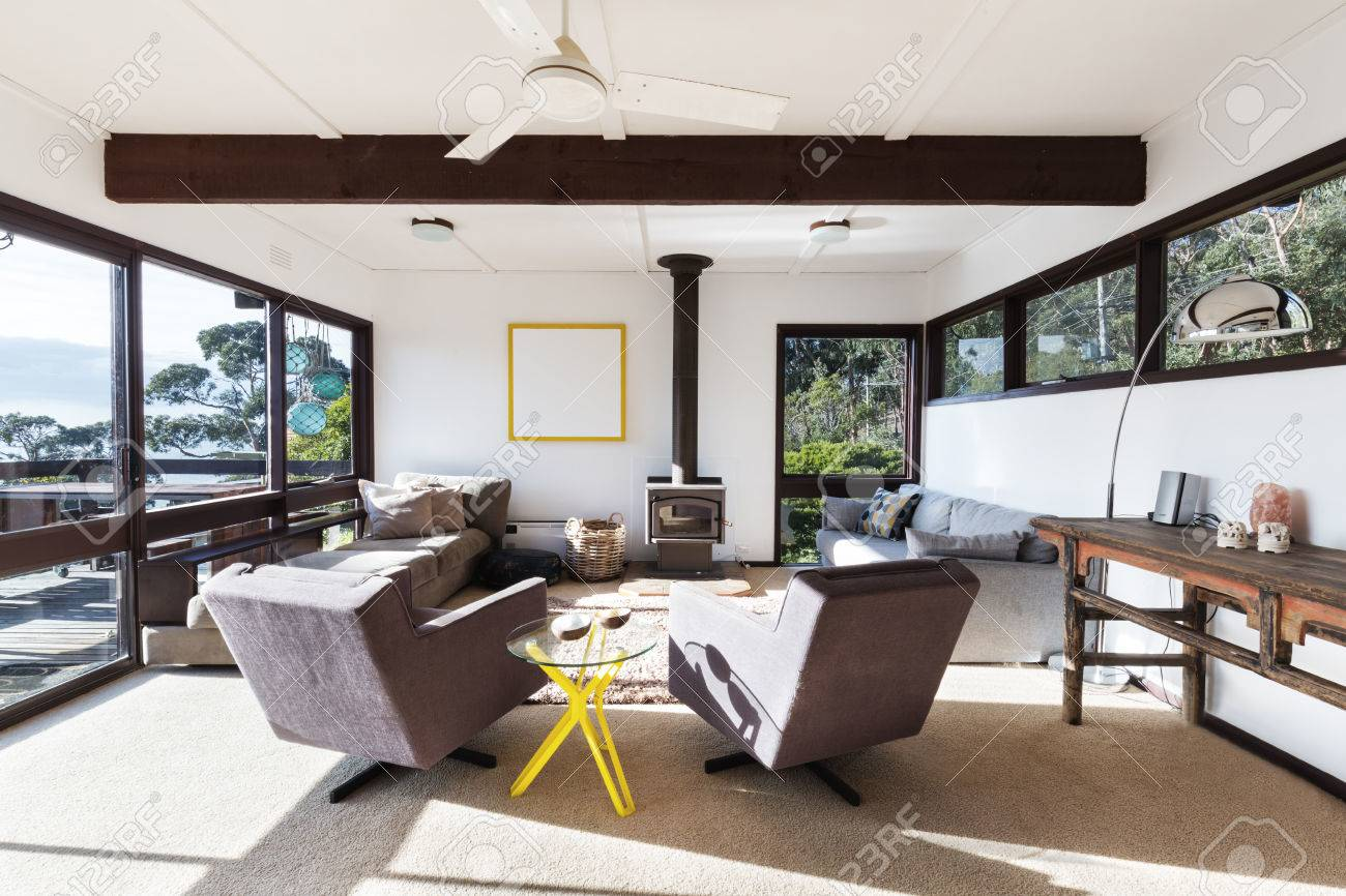 Funky retro beach house living room with 70s style recliner chairs and amazing views - 63226027