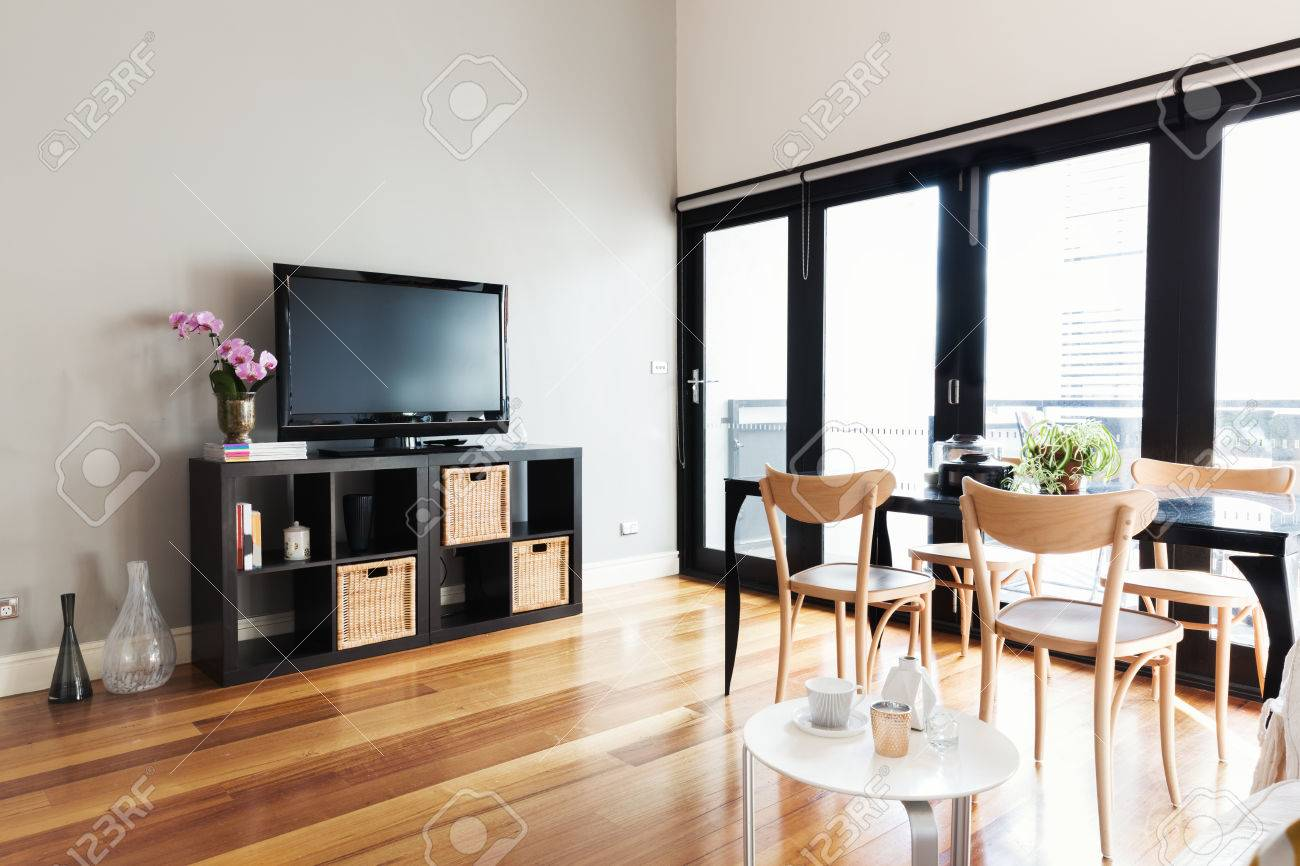 modern apartment living room with tv on buffet and bi fold door