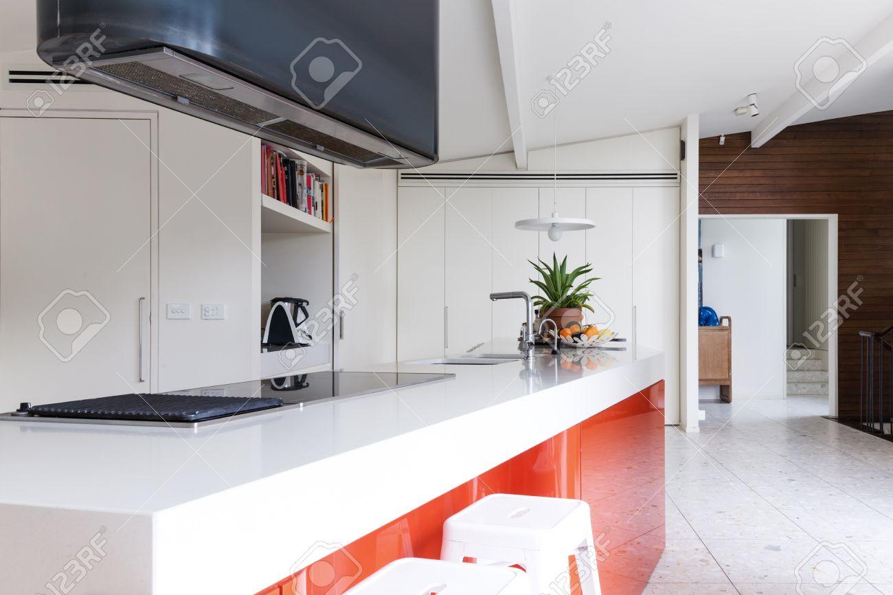 Kitchen Island Close Up close up of modern kitchen island bench with orange accent panel