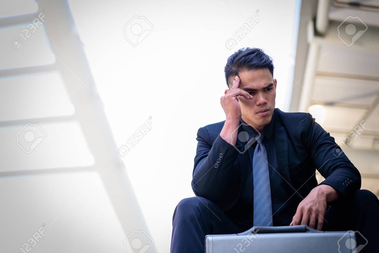 Asian Businessman feel sad and frustrated upset fail in life