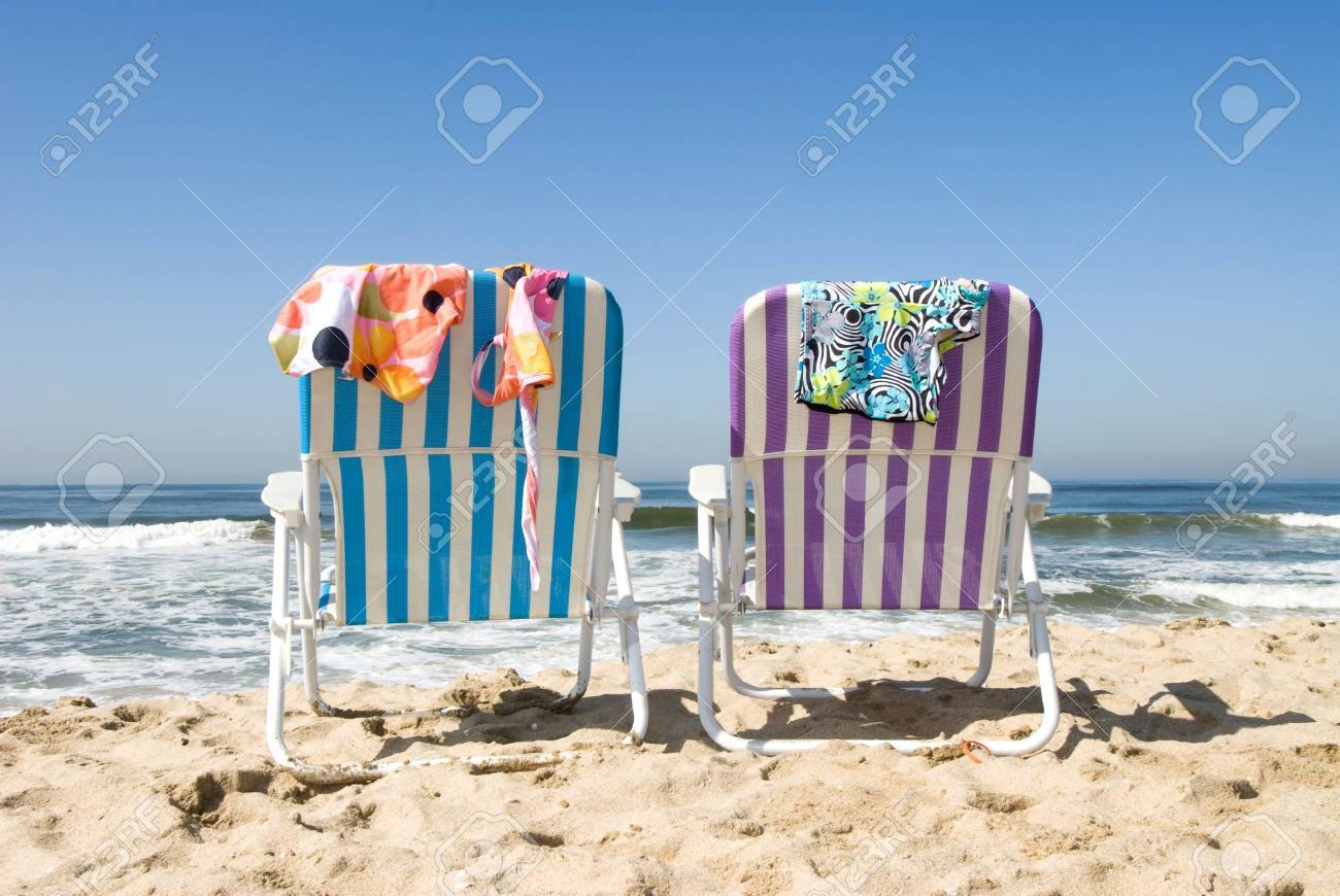 Two Beach Chairs With Bathing Suits Draped Over Them Insinuate ...