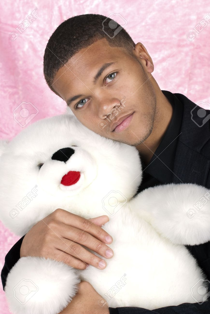 African American man cuddles with his large, white teddy bear during Valentines. Stock Photo - 4864248