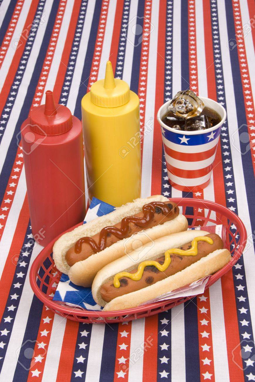 A picnic table with a patriotic table cloth hosts a basket of hotdogs with ketchup and mustard bottles and a cold soday. Stock Photo - 5231647