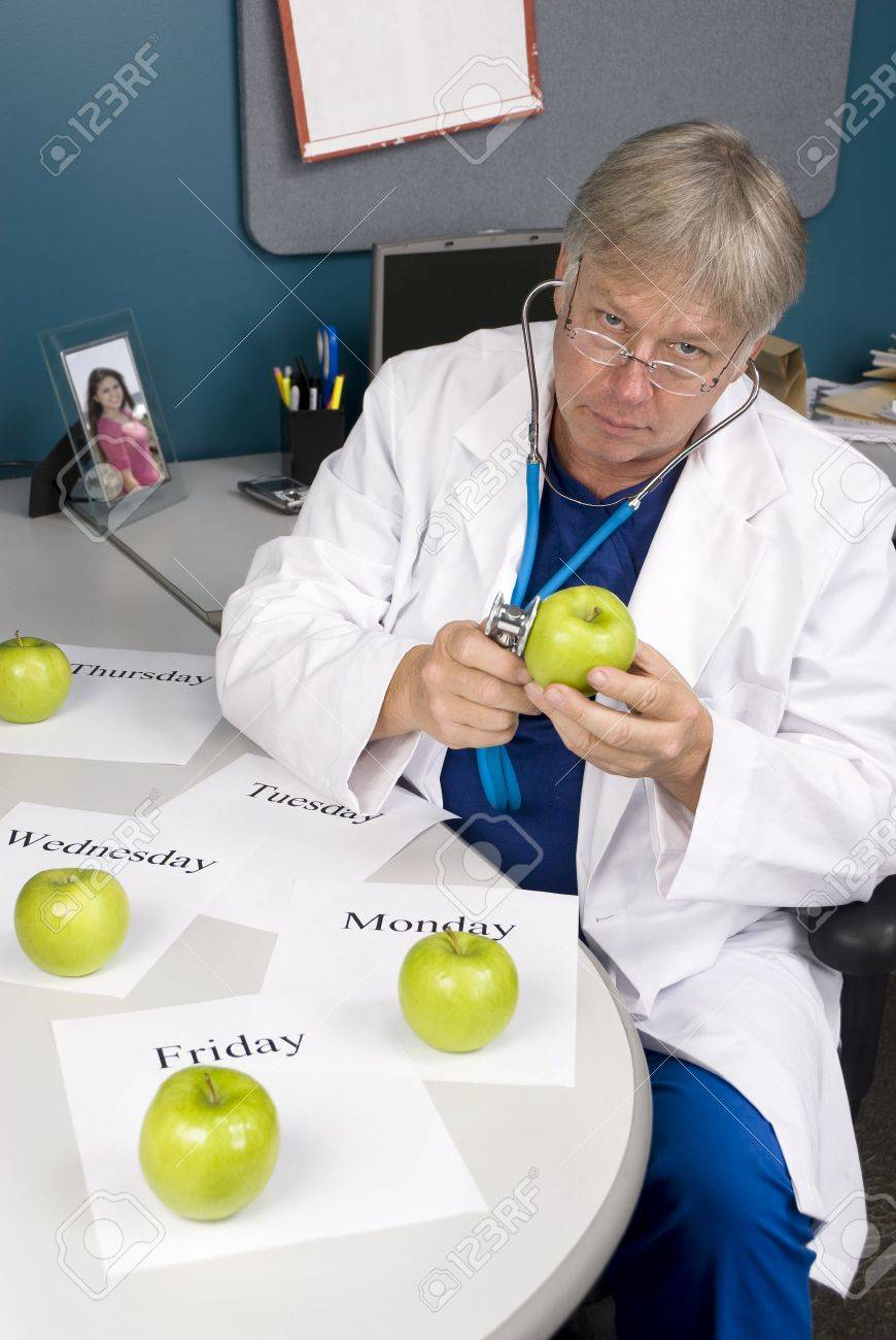 A doctor examines an apple with his stethoscope.  Image is useful for any healthy diet or eating inference. Stock Photo - 5529872