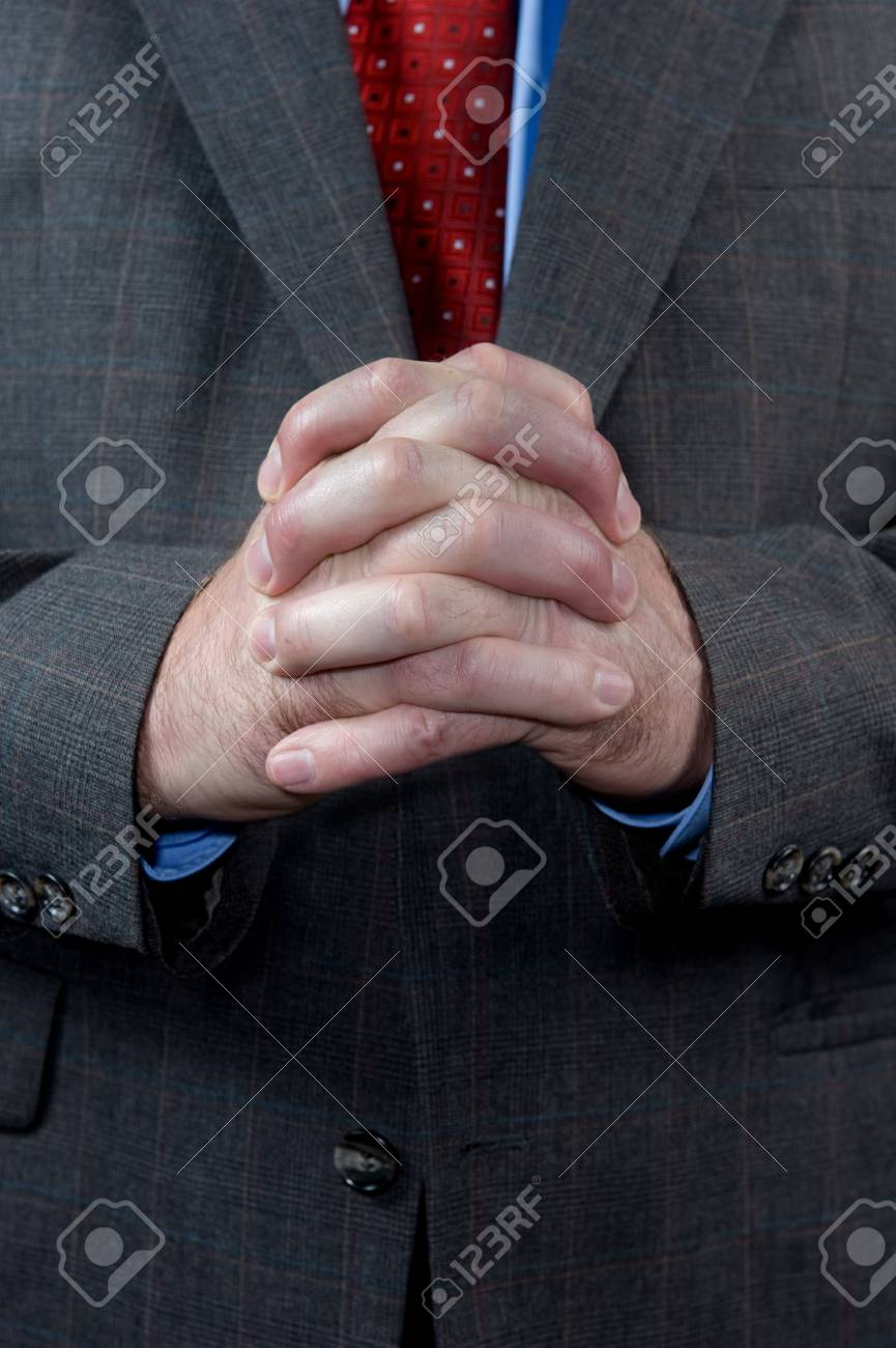 A well dressed businessman in his business suit waits and hopes while standing with his hands clasped. Stock Photo - 6862700