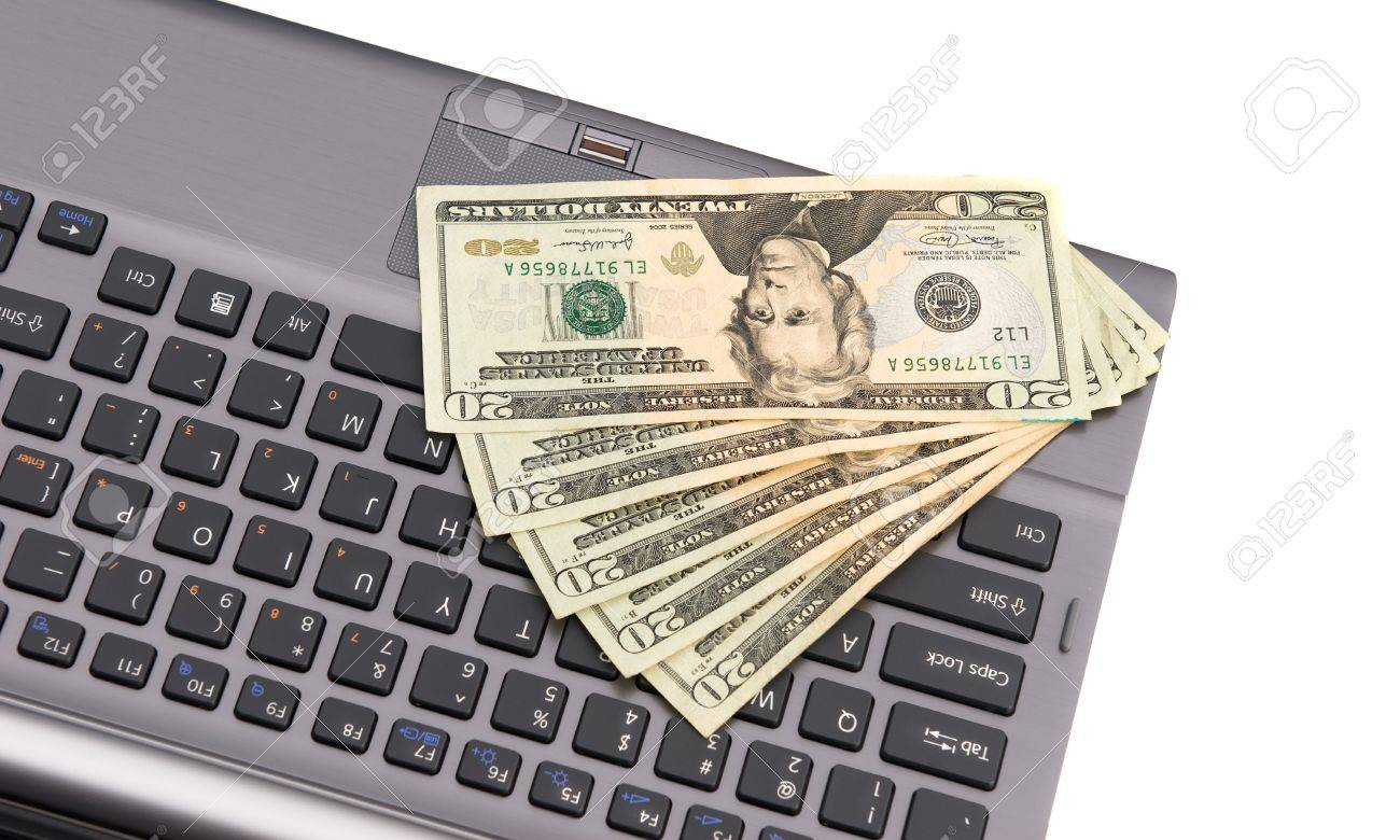 Cash lying on a keyboard during an online Internet shopping spree. Stock Photo - 7443869