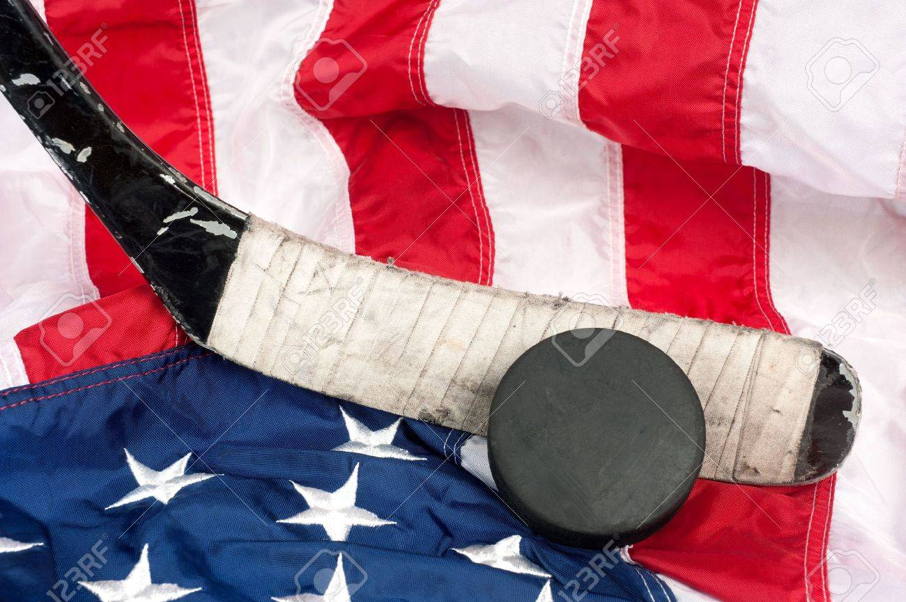 Hockey equipment including a stick and puck on an American flag to infer a patriotic American sport. Stock Photo - 7909525