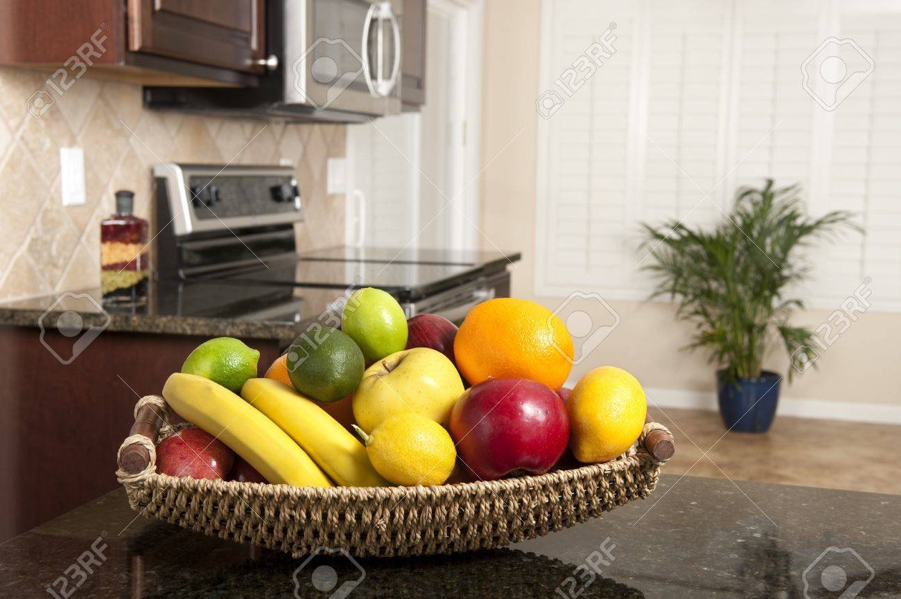 A fresh fruit basket on a granite countertop in a newly remodeled..