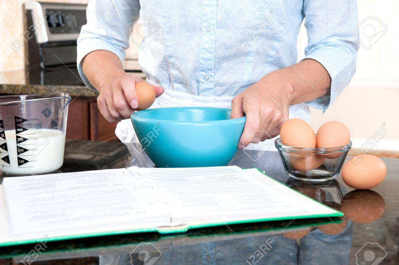 A homemaker cracks an egg into a mixing bowl while following the instructions of a cookbook. - 8430359