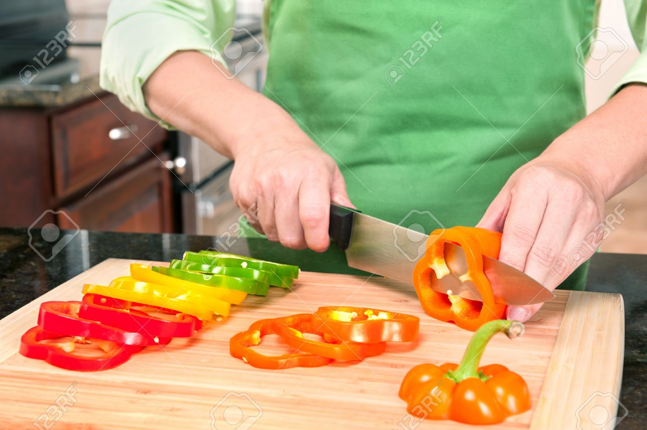 a woman slicing bell peppers prepares the vegetables as meal stock