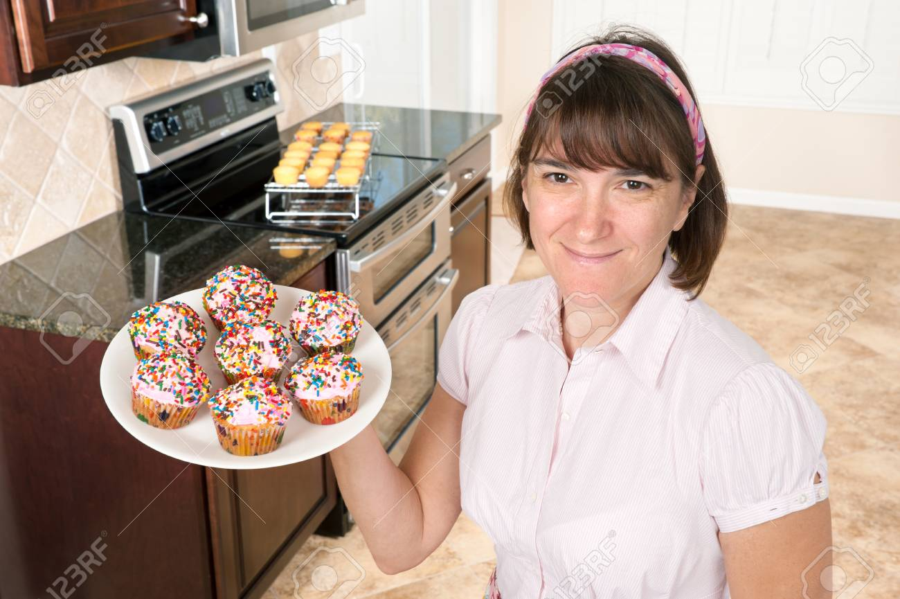 A homemaker shows off her decorated cupcakes with pink icing and candy sprinkles. Stock Photo - 8460452