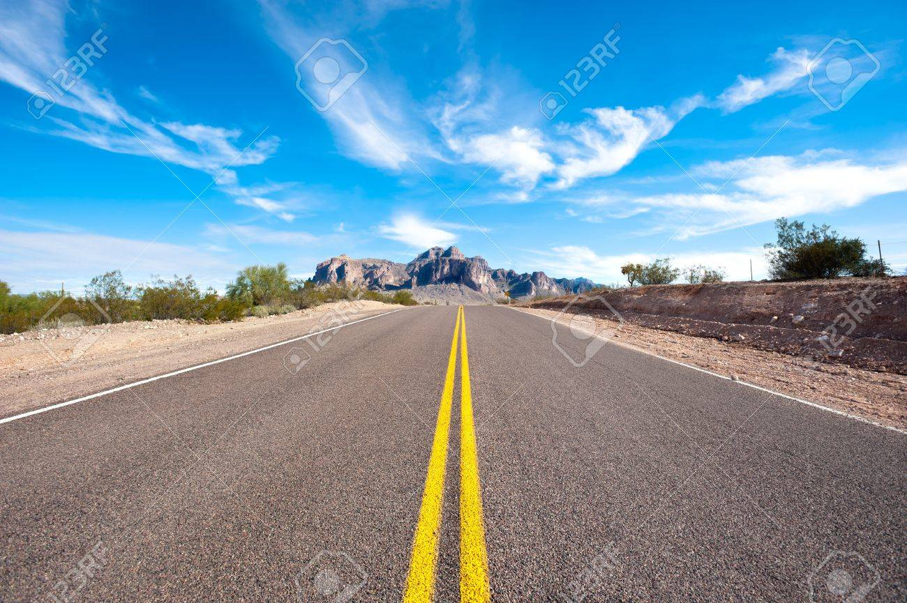 A remote and deserted desert road with a beautifyl sky. - 8622648
