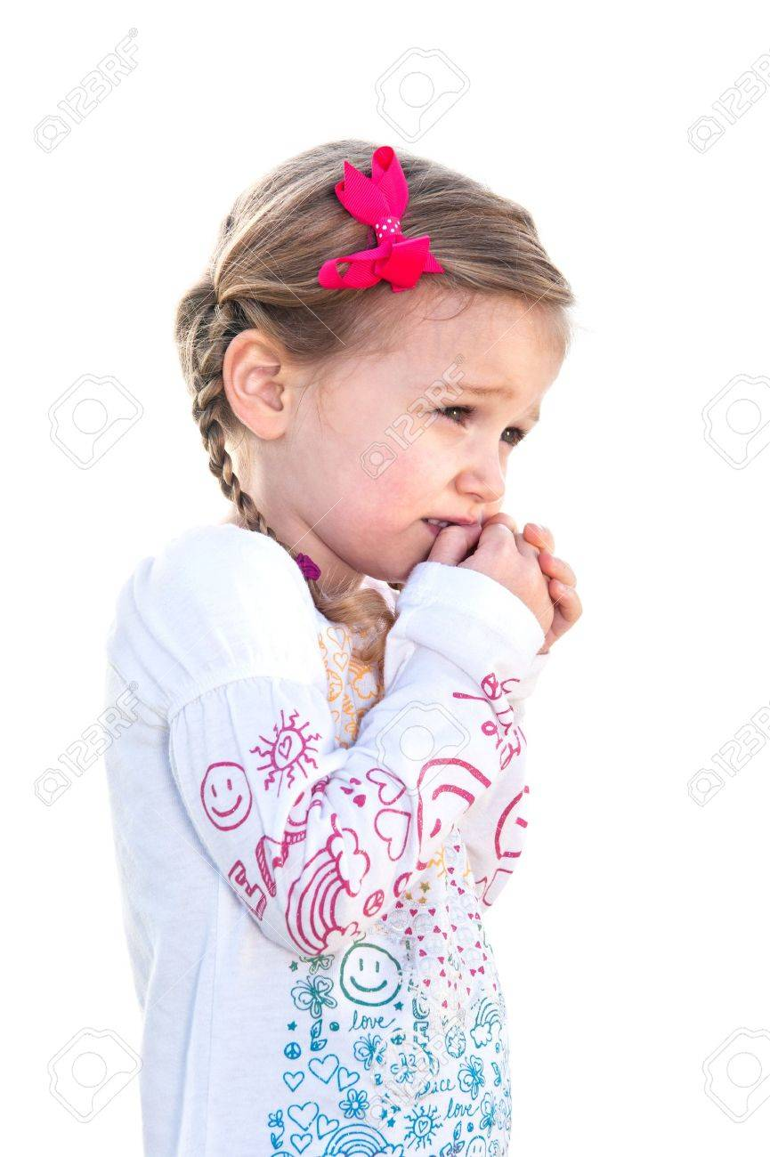 A beautiful little girl on a white background is frightened and holds her hand to her face. - 9139349