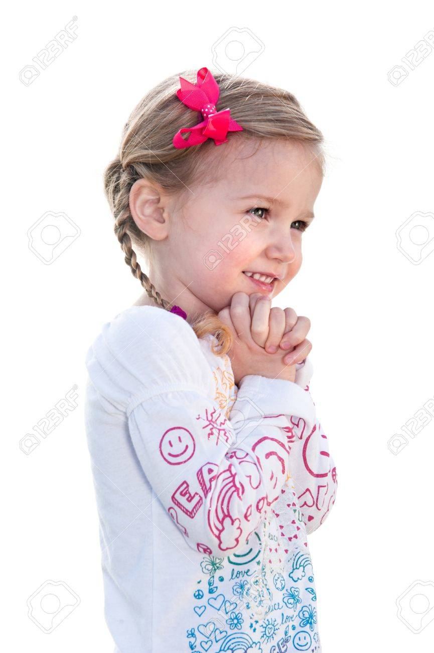 A beautiful little girl on a white background is happy and holds her hand to her face. - 9139346