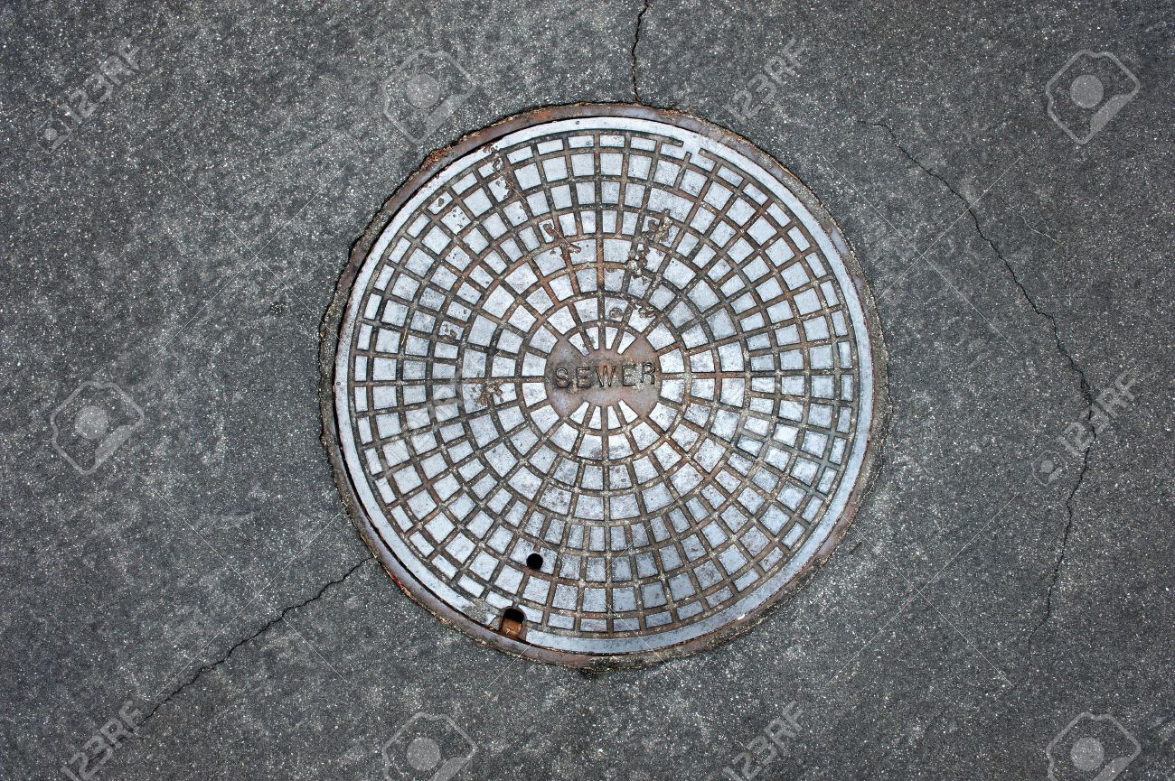 An old sewer manhole coversurrounded by an asphalt street - 10487851