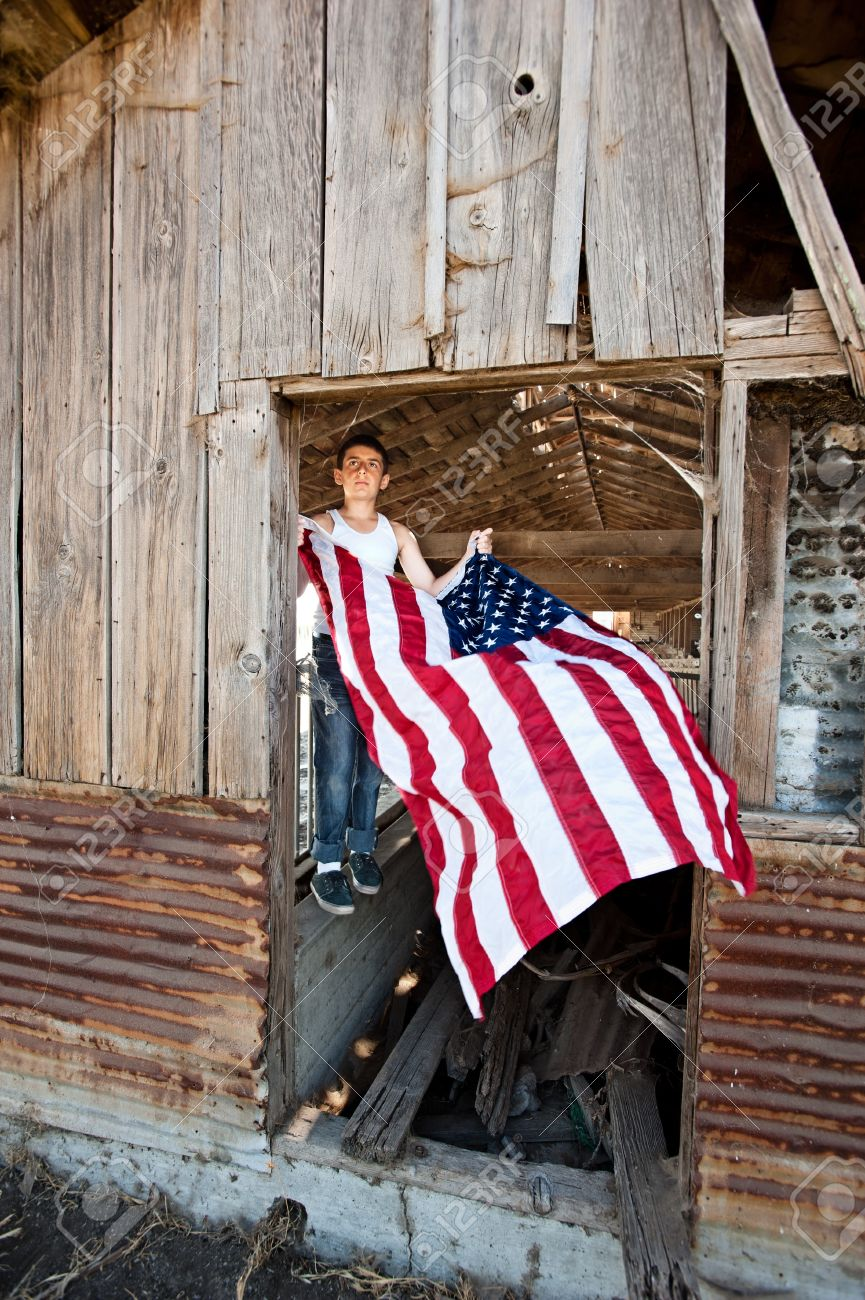 A Patriotic Teenager Gets Ready To Hang An American Flag On Old Rustic Barn Stock