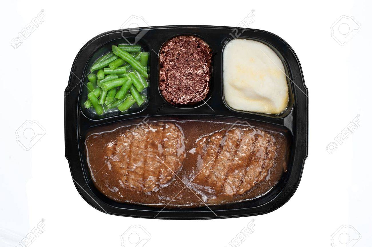 An unhealthy Salidbury steak TV dinner with gravy, mashed potatoes and a brownie dessert in a plastic tray isolated on white - 10896972