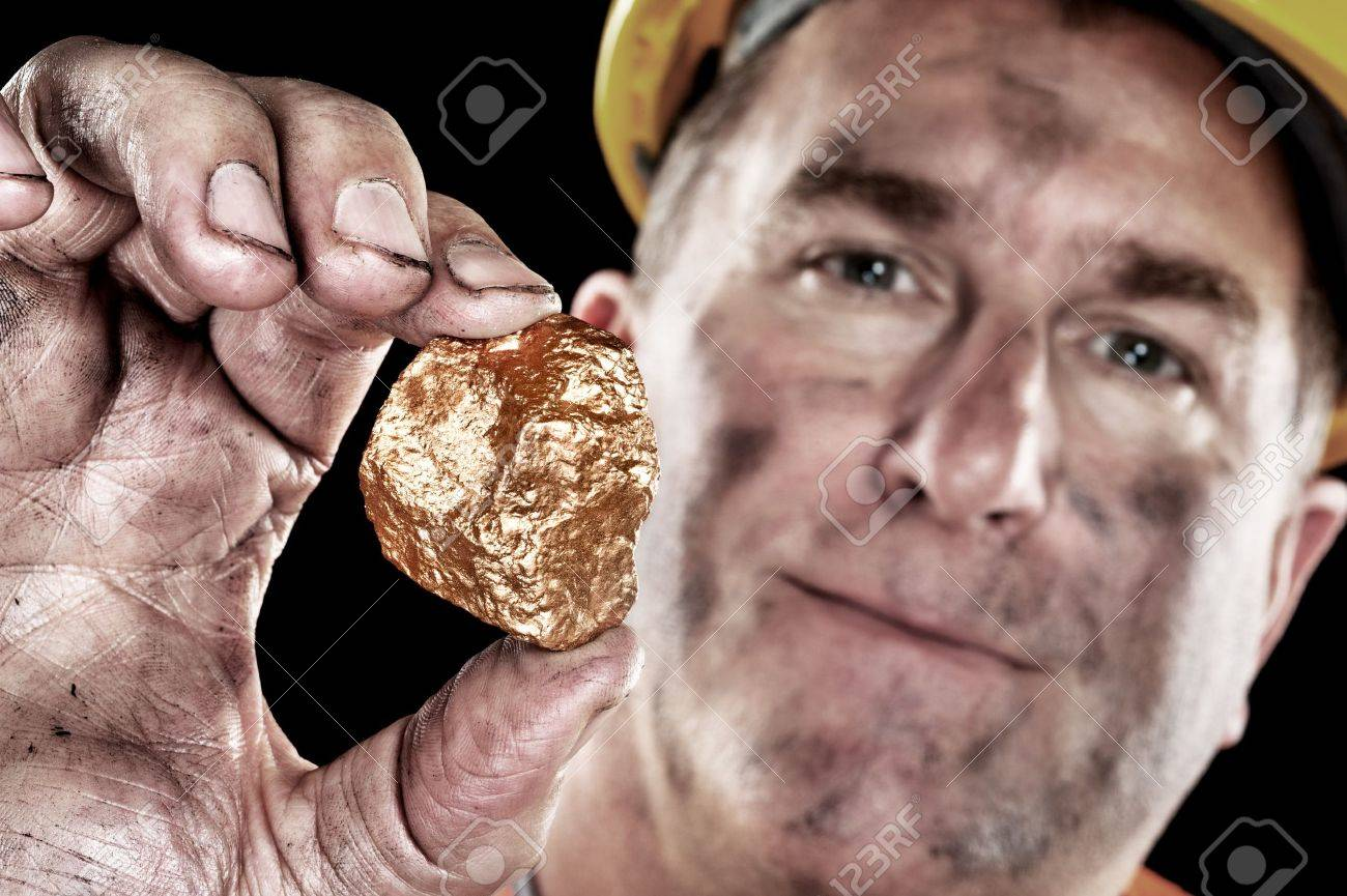 A gold miner shows a golden hugget freshly excavated from a mine. - 11199779