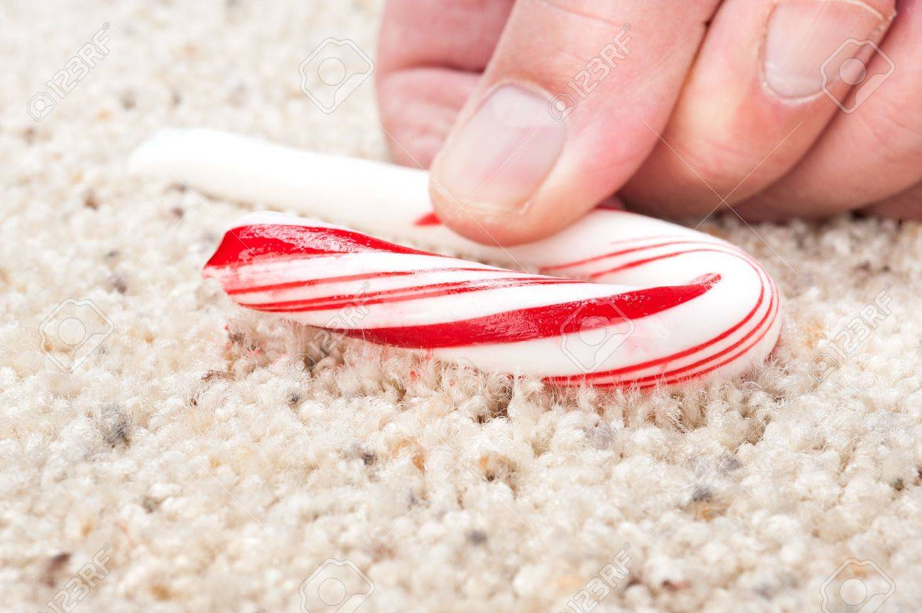 A man picks up a dropped candy cane that is stick to carpet fibers. - 11199719
