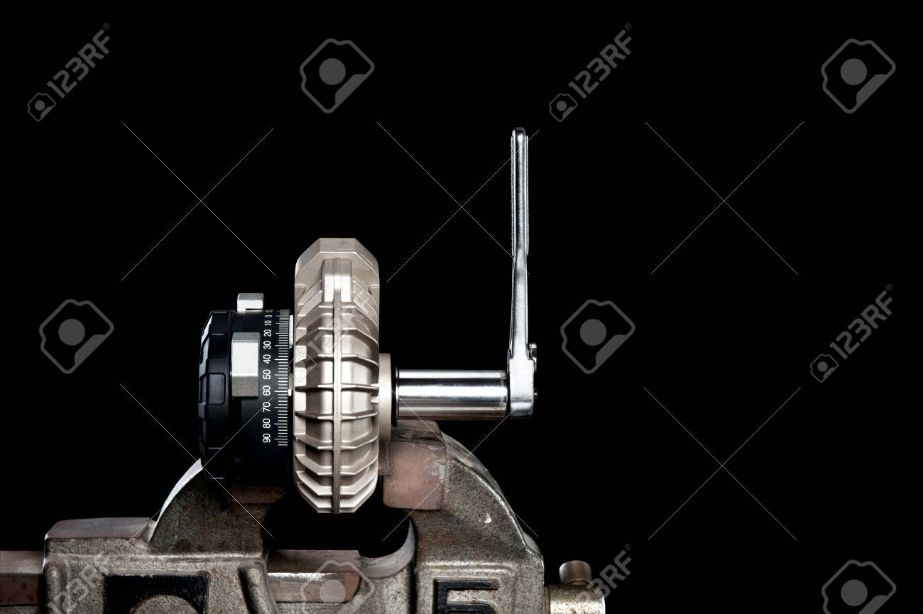 A small mechanical pump in a vice isolated on black for placement of copy. Stock Photo - 12461030