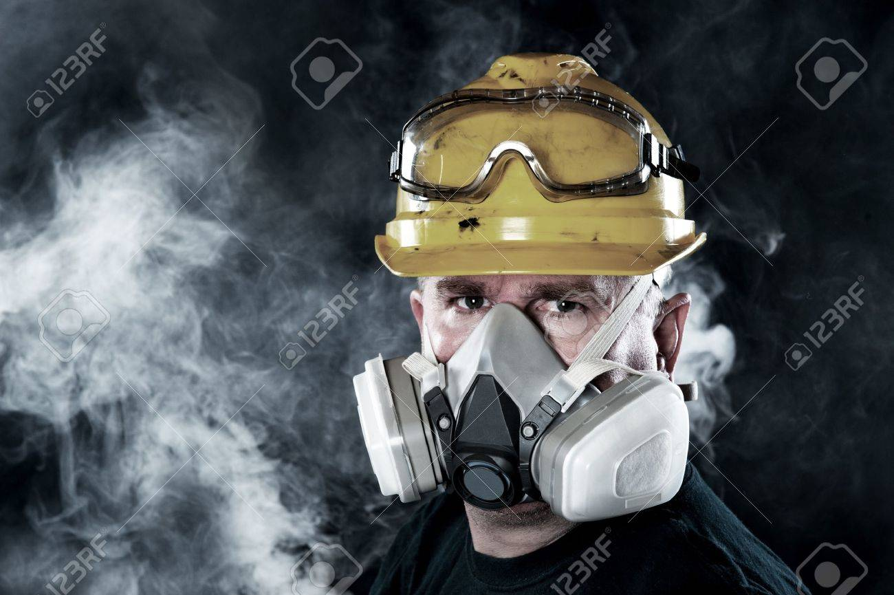 A rescue worker wears a respirator in a smokey, toxic atmosphere.  Image show the importance of protection readiness and safety. Stock Photo - 13998401
