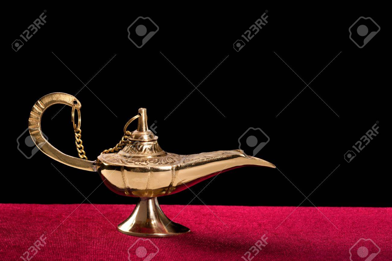 A Golden Genie Lamp On Red Velvet Against A Black Background. Designers  Have The Option