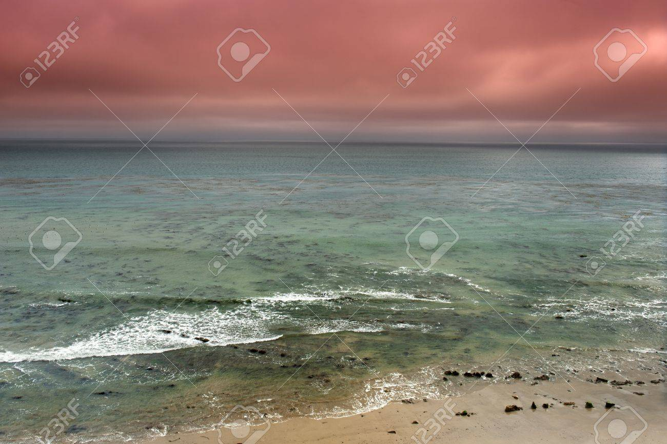 A dark, red storm moving in across a green ocean. Ripples on the water indicate windy conditions as the storm moves in.  Shot in Southern California, Santa Barbara. Stock Photo - 19603864