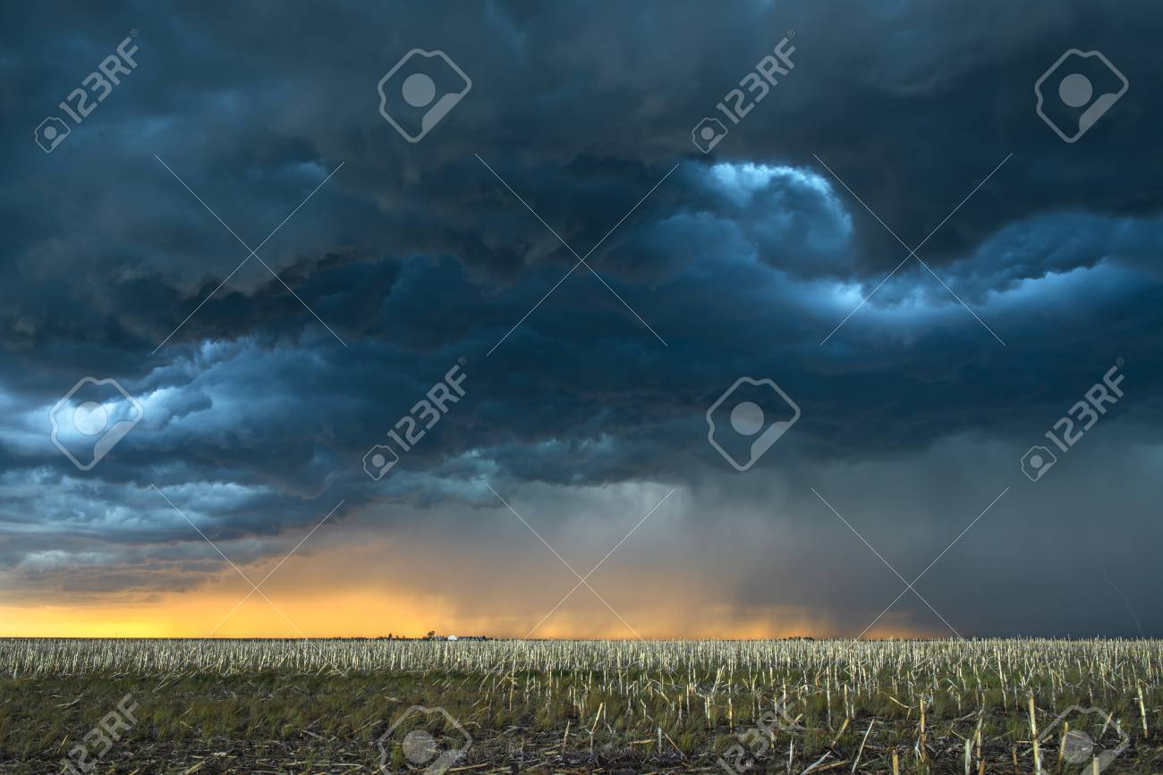 A mezocyclone storm with dark, gray clouds forming over the plains in Tornado Alley, Oklahoma at sunset - 105327743