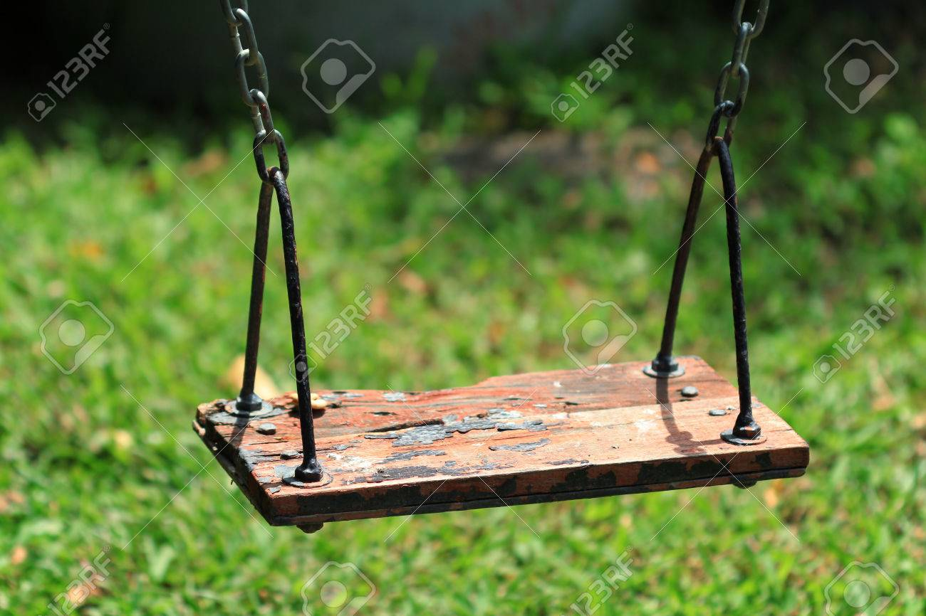 Old wood swing hanging in garden, green background. Stock Photo - 24501178