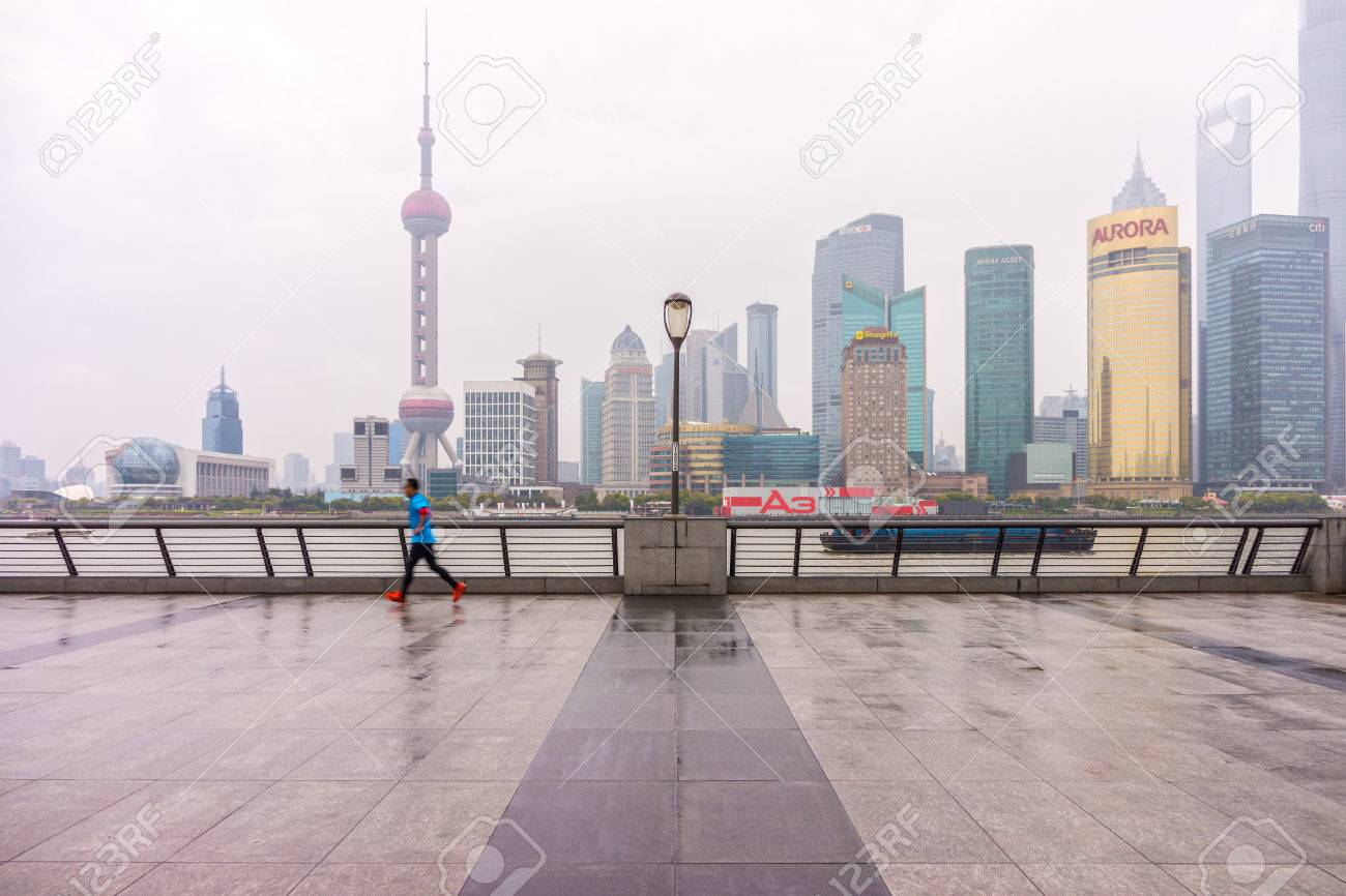 SHANGHAI, CHINA - MARCH 28, 2014: People exercise on the Bund in the morning opposite Pudong landmarks. - 37080202