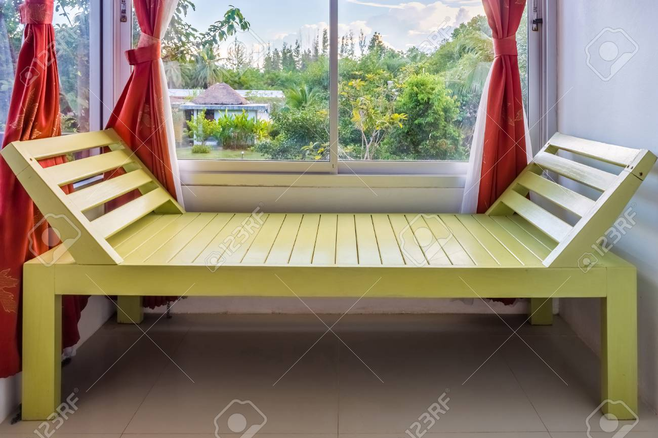Modern green wooden bench nearby window it is furniture for interior decoration stock photo