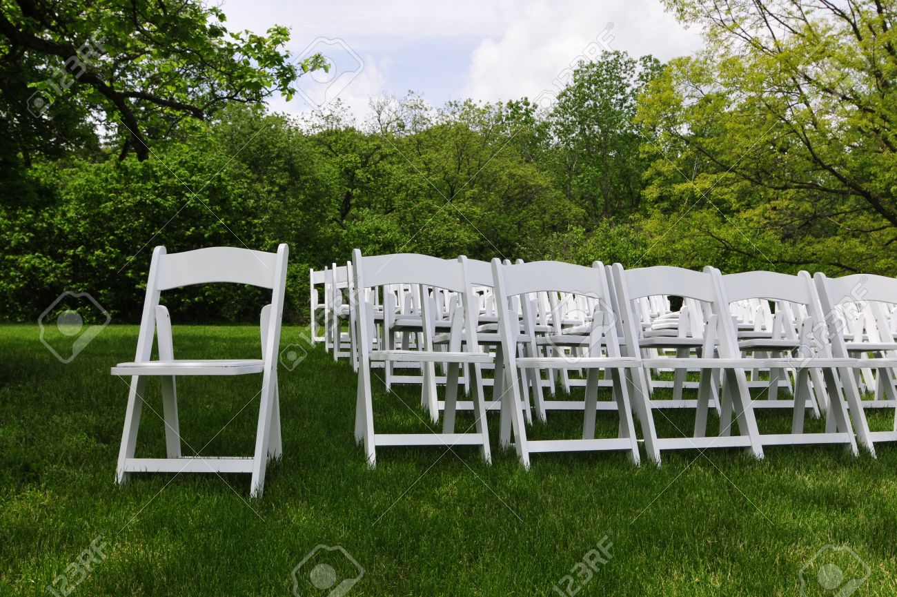 Rows Of White Folding Chairs From An Outdoor Wedding