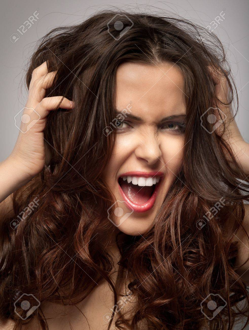 Very frustrated and angry mad woman hands in her hair pulling. Isolated on grey background. Stock Photo - 12145485