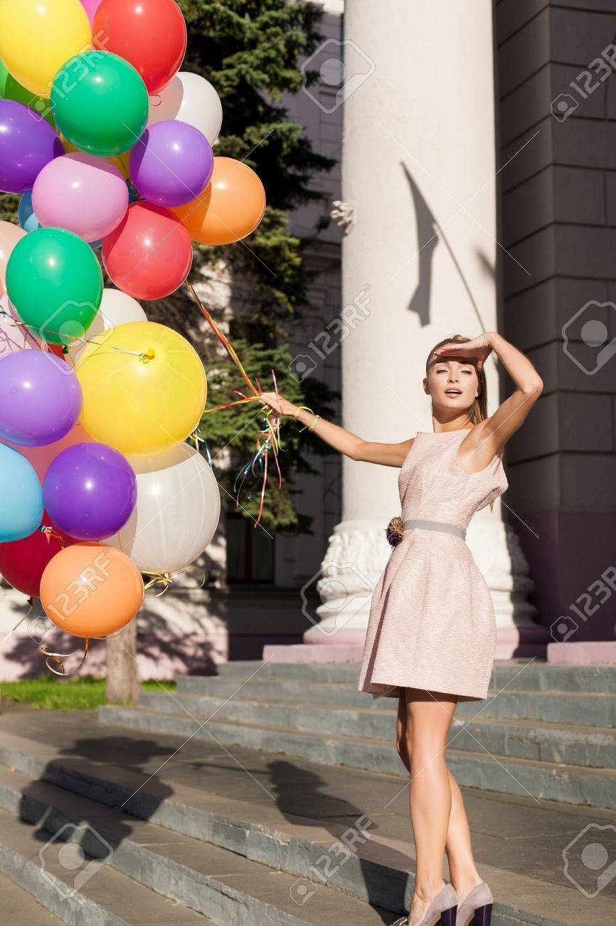 Young sexy woman with colorful latex balloons looking at the sun, urban scene, outdoors Stock Photo - 15465176