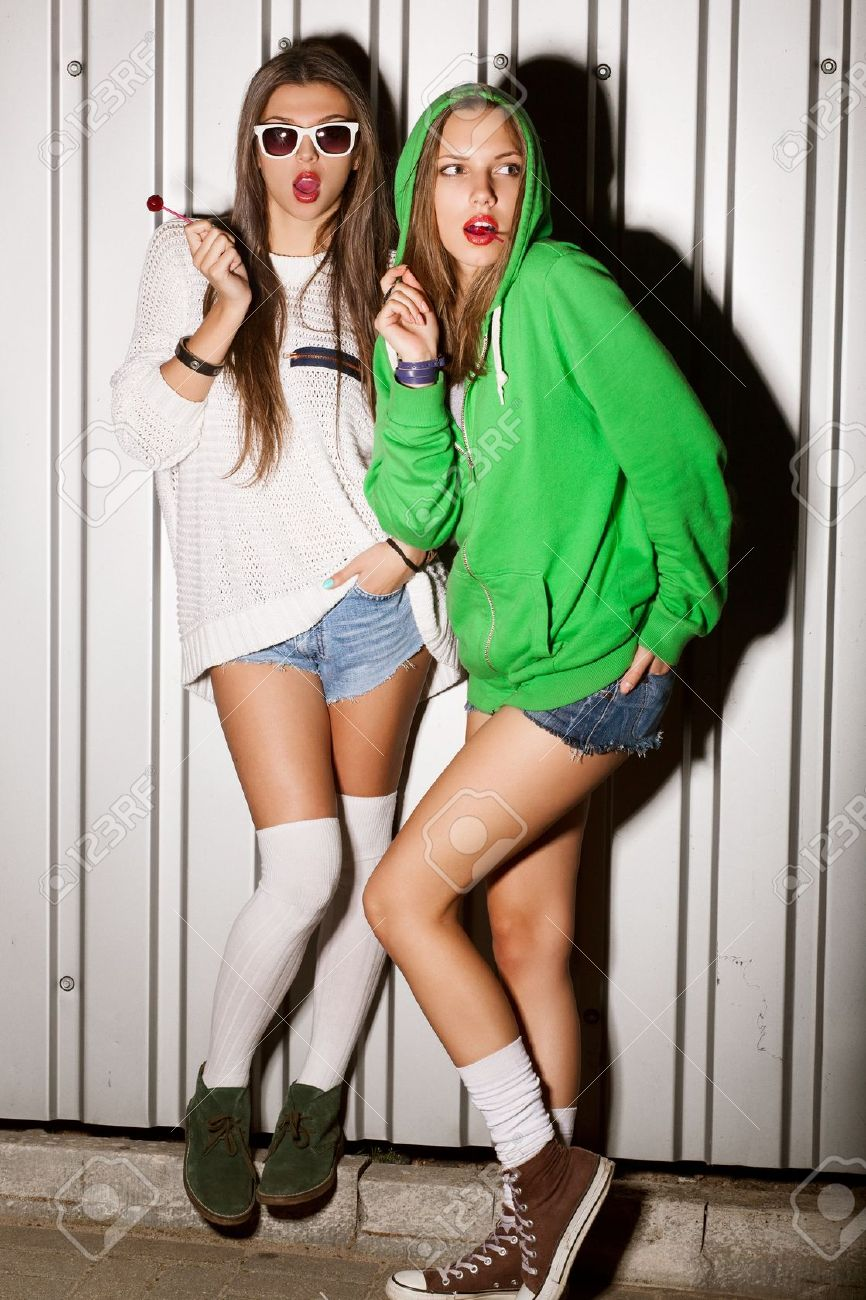 Portrait of two young good looking girls sucking lollipops, outdoors Stock Photo - 15896164