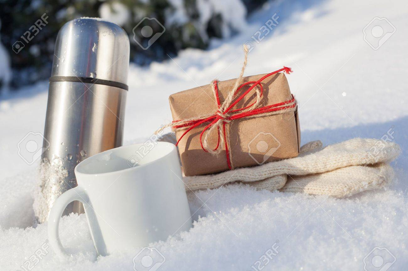 Gift box with cup and mittens in snow on a background of a winter landscape, outdoors Stock Photo - 17511905