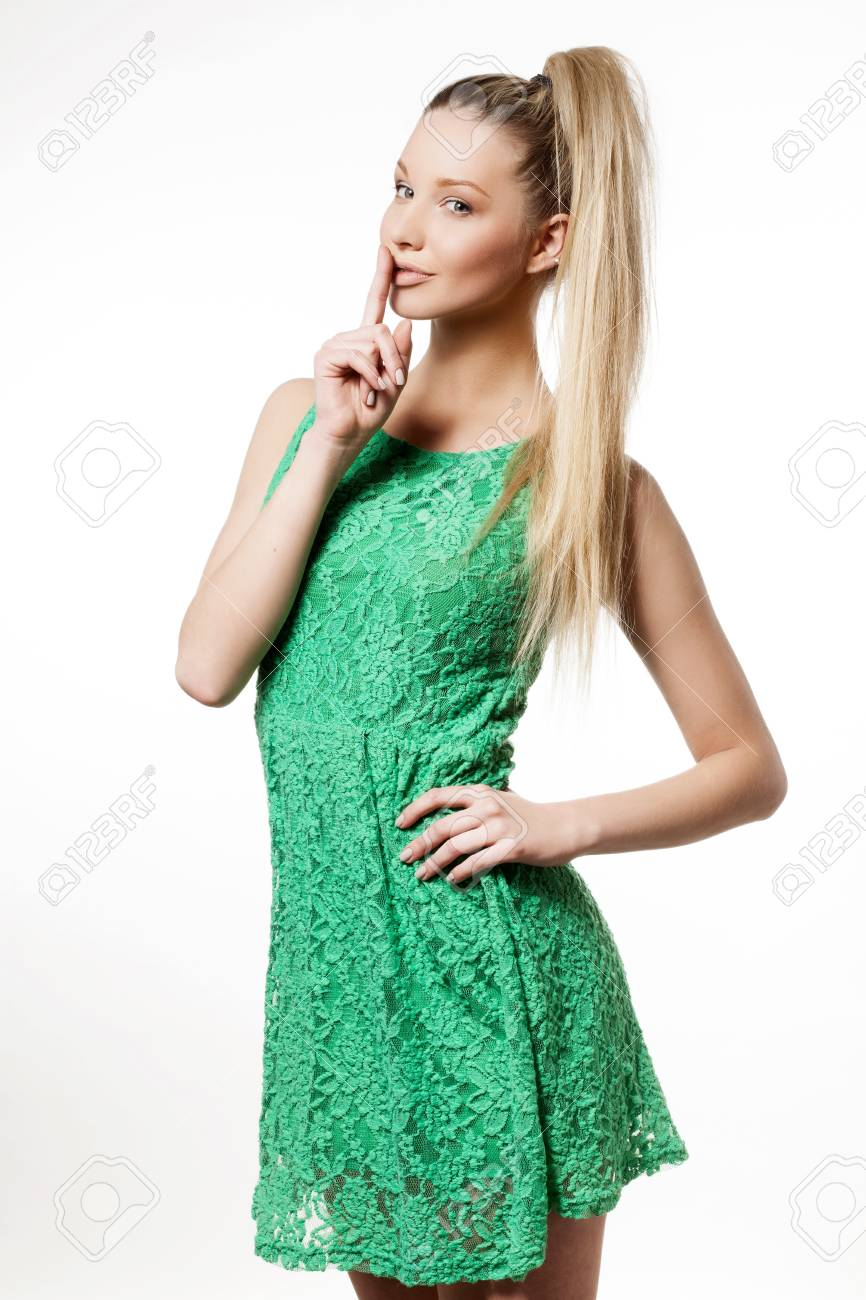 25914f5ce Portrait Of A Young Woman In Green Dress Making A Hush Gesture ...
