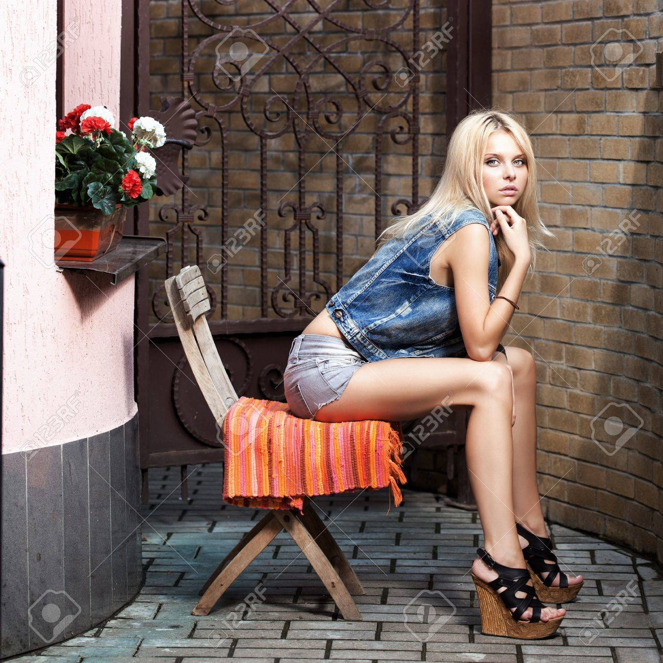 Stock Photo - Young blonde woman sitting on the chair with long sexual legs. Beautiful girl summer portrait toned with tender summer yellow color.  sc 1 st  123RF.com & Young Blonde Woman Sitting On The Chair With Long Sexual Legs ...