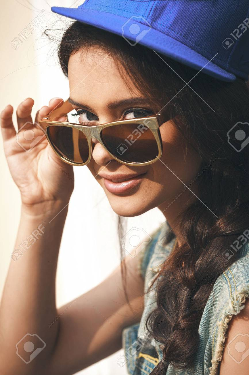 Closeup of Young sexy girl in blue cap and jeans jacket  looking through golden sunglasses .  Outdoors, lifestyle. Stock Photo - 23054283