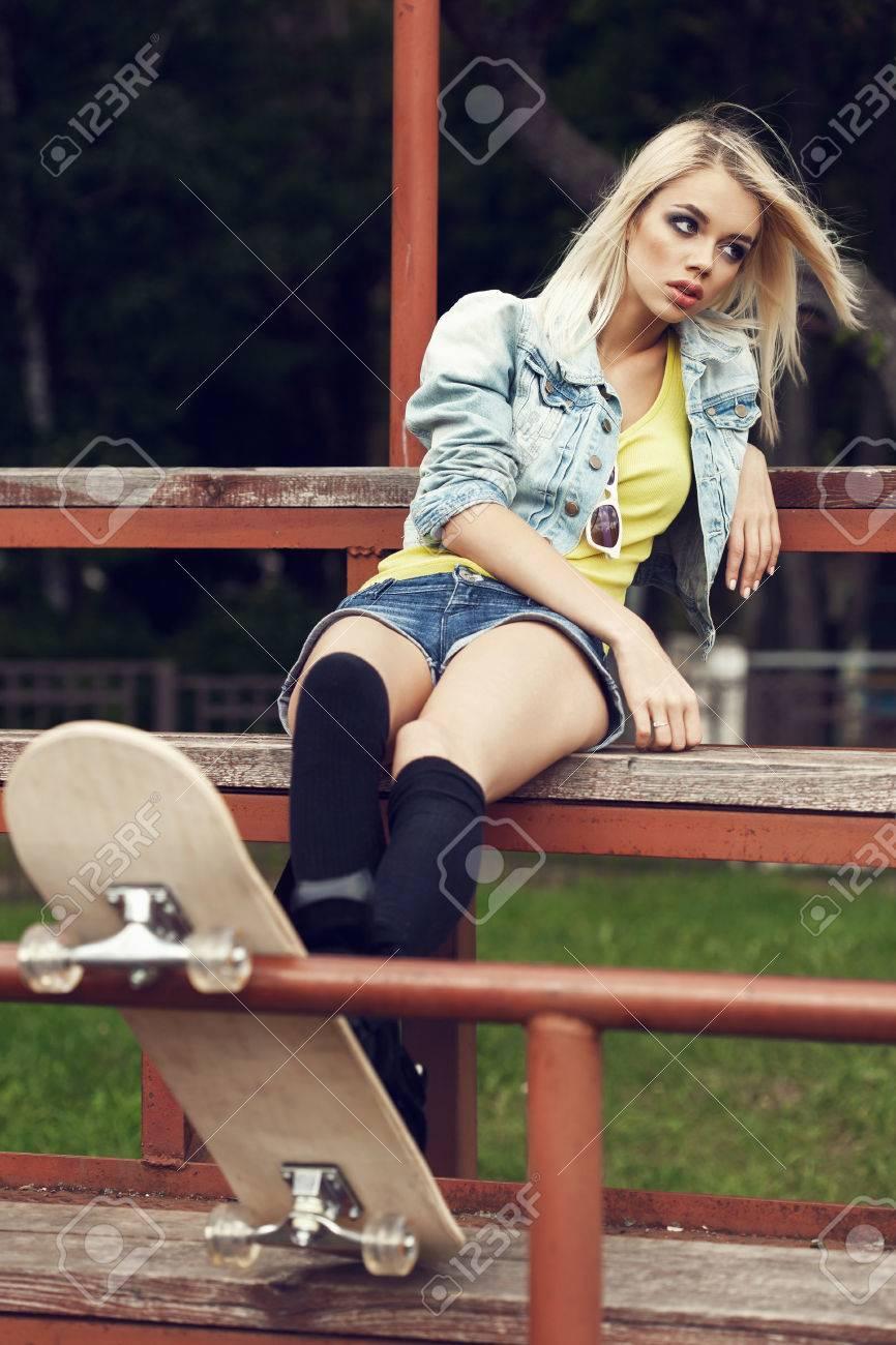 La Jolie Fille De L Air belle fille de détente en plein air. jolie fille assise dans la rangée de  sièges en bois au stade de l'école. reste de l'étude. extérieur, mode de vie
