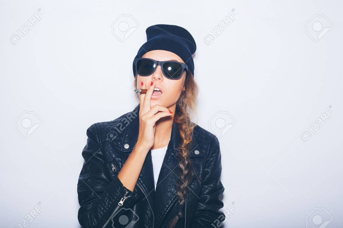 8d546294d Sexy girl in sunglasses and black leather jacket smoking cigar. White  background, not isolated
