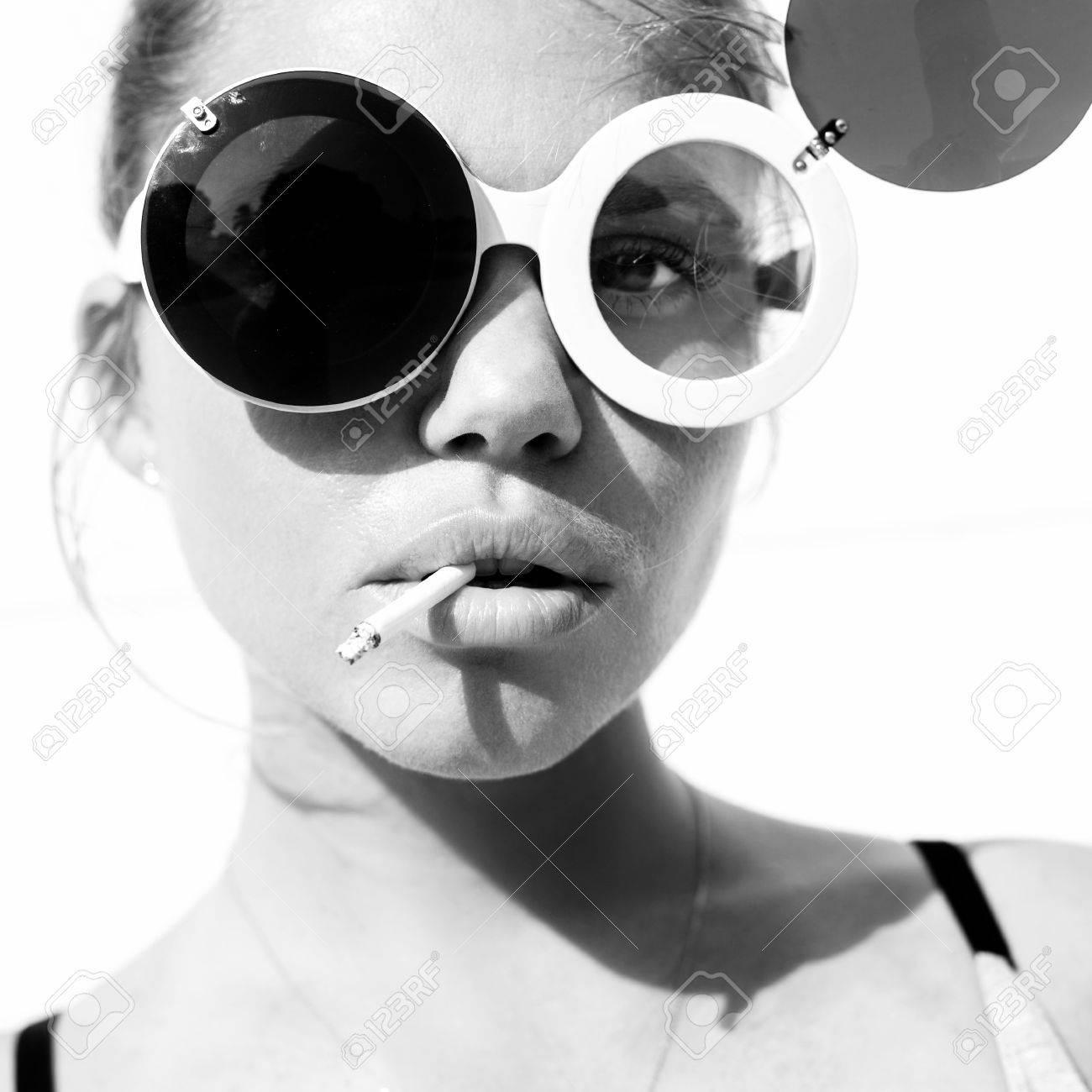 Banque d images - Close-up de la beauté fille dans lunettes de soleil  branchées avec la cigarette. Virage en noir et blanc. Fond blanc, pas isolé 7e8ae1faab41