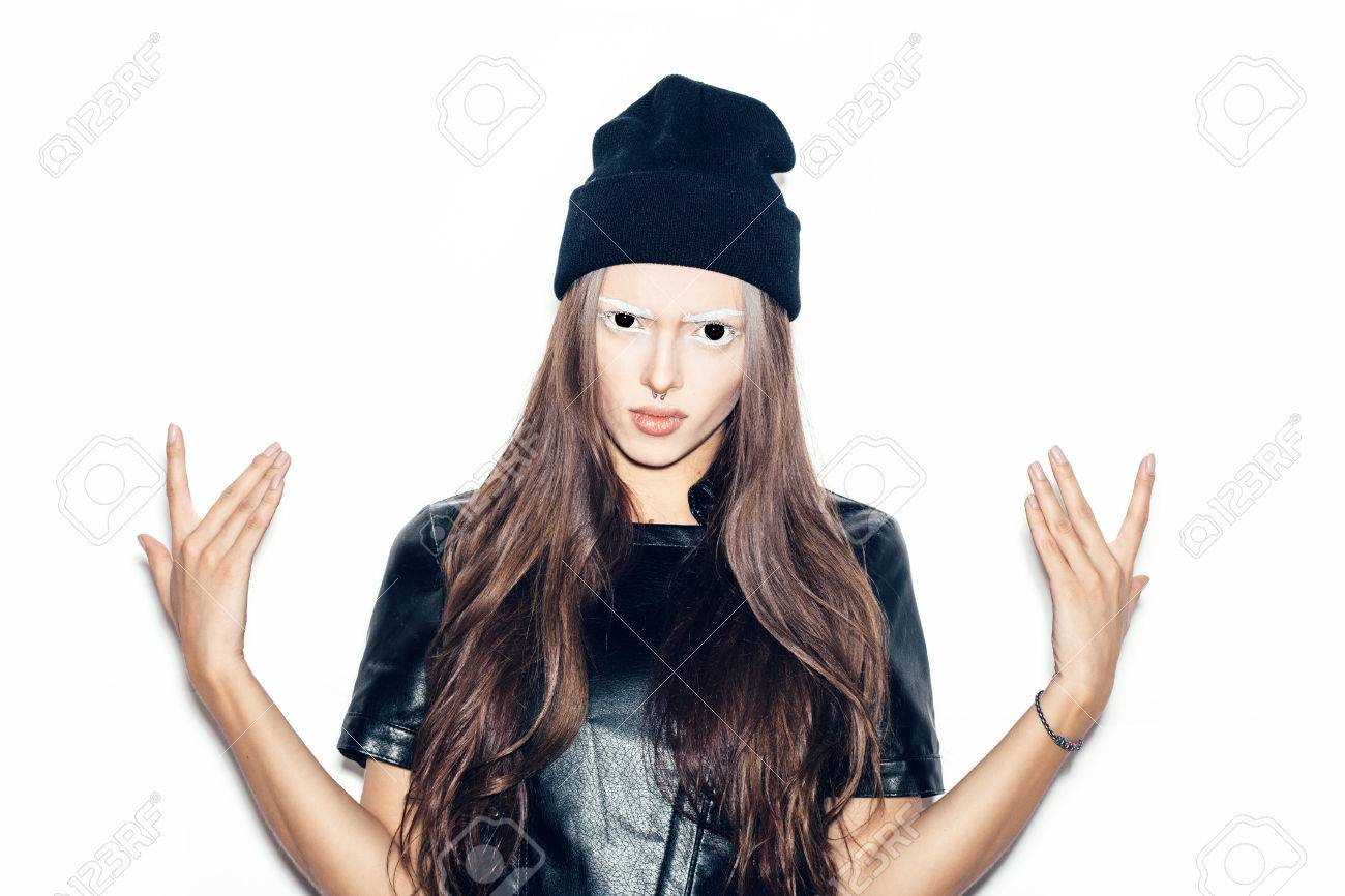 young beautiful woman in black beanie giving the rock and roll