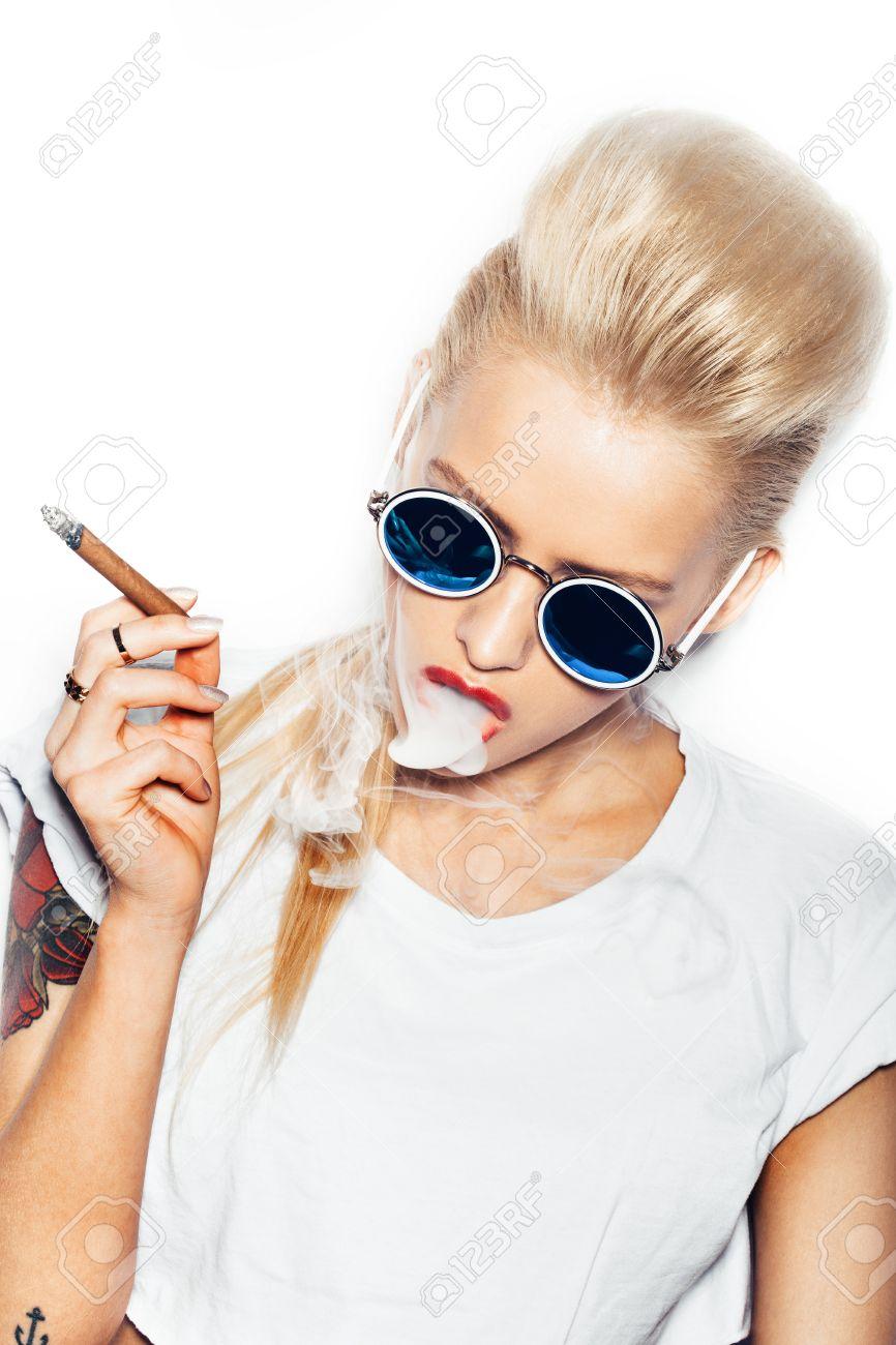 3c42bda78a180 Banque d images - Femme de style Swag des lunettes de soleil et t-shirt  blanc soufflant la fumée de cigare. Fond blanc
